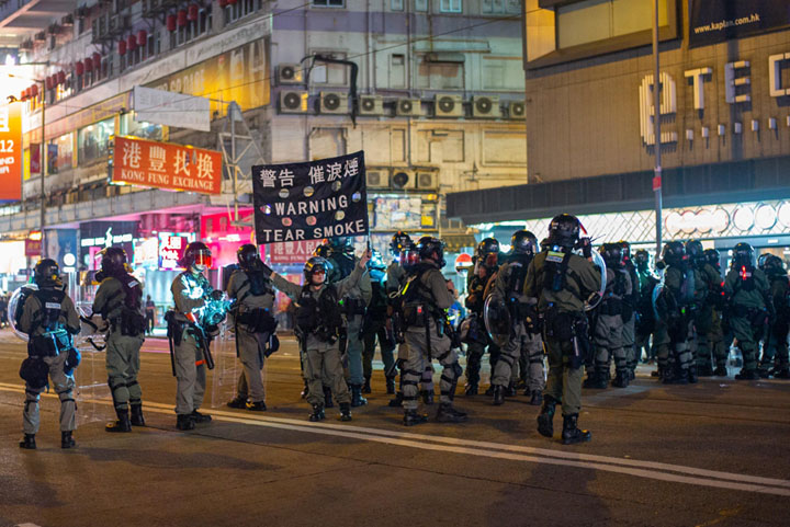 "Hong Kong police holding a ""warning: tear smoke"" sign"